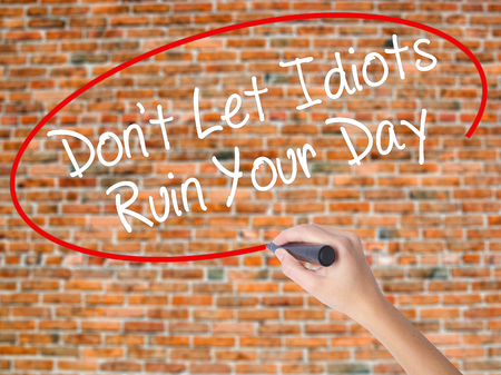 unprofessional: Woman Hand Writing Dont Let Idiots Ruin Your Day with black marker on visual screen. Isolated on bricks. Business concept. Stock Photo