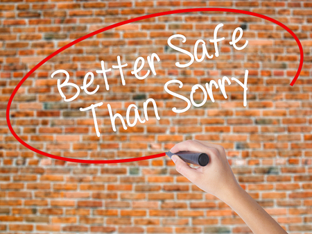 better safe than sorry: Woman Hand Writing Better Safe Than Sorry with black marker on visual screen. Isolated on bricks. Business concept. Stock Photo Stock Photo