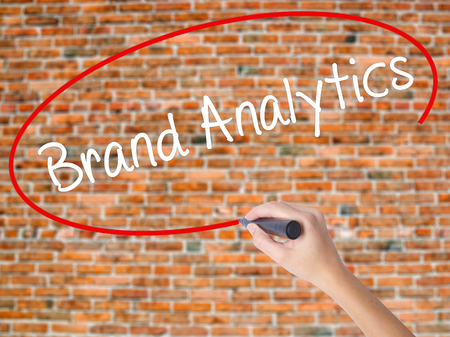 Woman Hand Writing Brand Analytics with black marker on visual screen. Isolated on bricks. Business concept. Stock Photo