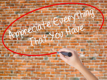 Woman Hand Writing Appreciate Everything That You Have with black marker on visual screen. Isolated on bricks. Business concept. Stock Photo Stock Photo