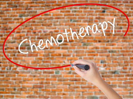 radiotherapy: Woman Hand Writing Chemotherapy with black marker on visual screen. Isolated on bricks. Business concept. Stock Photo