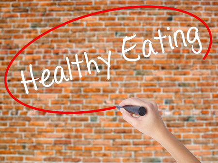 Woman Hand Writing Healthy Eating with black marker on visual screen. Isolated on bricks. Life, technology, internet concept. Stock Image