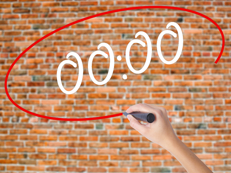 Woman Hand Writing 00:00  with black marker on visual screen. Isolated on bricks. Business concept. Stock Photo
