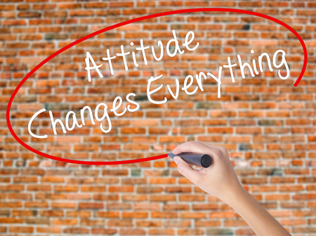 Woman Hand Writing Attitude Changes Everything with black marker on visual screen. Isolated on bricks. Business concept. Stock Photo