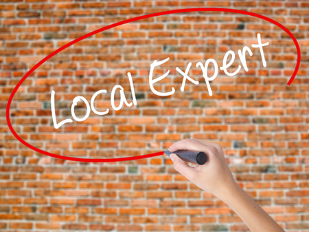 Woman Hand Writing  Local Expert with black marker on visual screen. Isolated on bricks. Business concept. Stock Photo