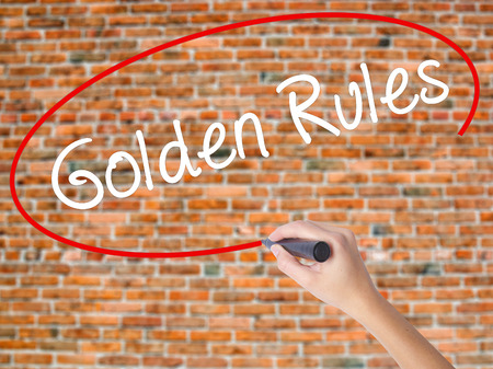 Woman Hand Writing Golden Rules with black marker on visual screen. Isolated on bricks. Business concept. Stock Photo