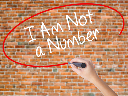 Woman Hand Writing I Am Not a Number with black marker on visual screen. Isolated on bricks. Business concept. Stock Photo