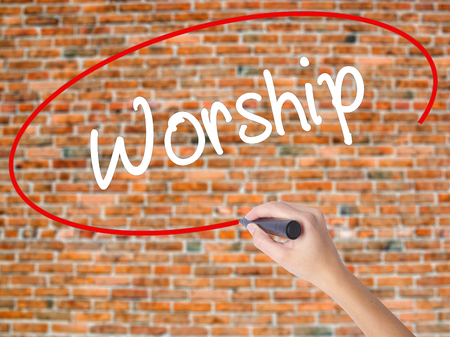Woman Hand Writing Worship with black marker on visual screen. Isolated on bricks. Business concept. Stock Photo Stock Photo