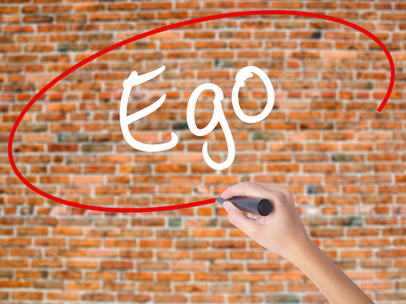 Woman Hand Writing Ego with black marker on visual screen. Isolated on bricks. Business concept. Stock Photo