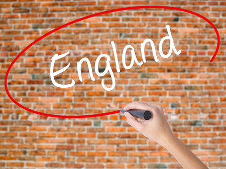 Woman Hand Writing England with black marker on visual screen. Isolated on bricks. Business concept. Stock Photo Stock Photo