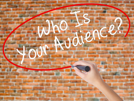 Woman Hand Writing Who Is Your Audience? with black marker on visual screen. Isolated on bricks. Business concept. Stock Photo