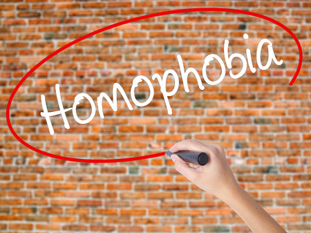 homophobia: Woman Hand Writing Homophobia with black marker on visual screen. Isolated on bricks. Business concept. Stock Photo Stock Photo