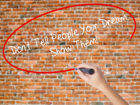 Woman Hand Writing Dont Tell People Your Dream. Show Them! with black marker on visual screen. Isolated on bricks. Business, technology, internet concept.