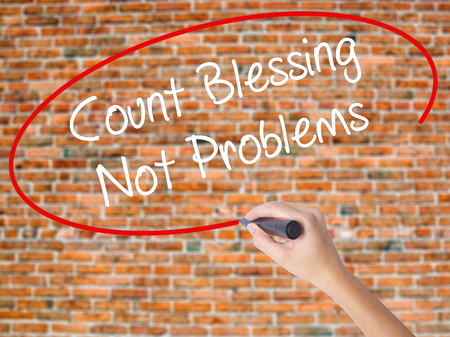 Woman Hand Writing Count Blessing Not Problems with black marker on visual screen. Isolated on bricks. Business concept. Stock Photo