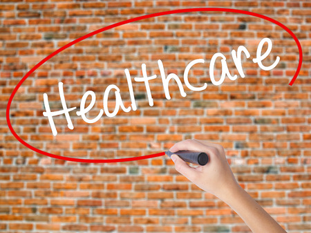 Woman Hand Writing Healthcare with black marker on visual screen. Isolated on bricks. Business concept. Stock Photo