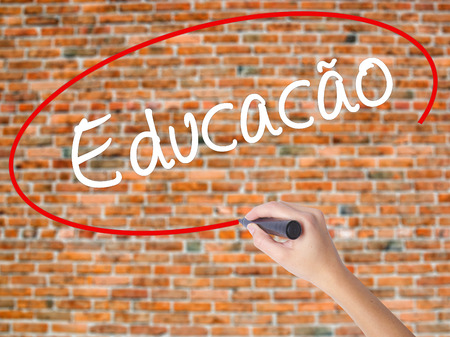 Woman Hand Writing Education (Educacao in Portuguese) with black marker on visual screen. Isolated on bricks. Business concept. Stock Photo Stock Photo