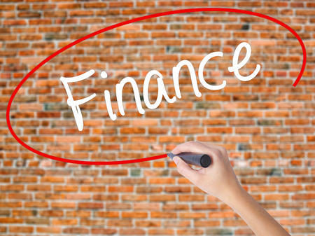 Woman Hand Writing Finance with black marker on visual screen. Isolated on bricks. Business concept. Stock Photo Stock Photo