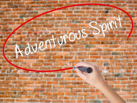 Mano de mujer escribiendo espíritu aventurero con marcador negro en la pantalla visual. Aislado en ladrillos. Concepto de negocio. Foto de stock