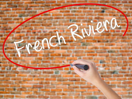 Woman Hand Writing French Riviera with black marker on visual screen. Isolated on bricks. Business concept. Stock Photo