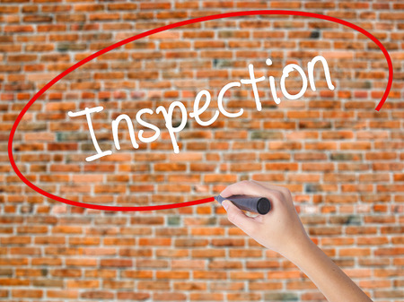 warranty questions: Woman Hand Writing Inspection with black marker on visual screen. Isolated on bricks. Business concept. Stock Photo Stock Photo