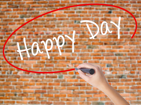 Woman Hand Writing  Happy Day with black marker on visual screen. Isolated on bricks. Business concept. Stock Photo