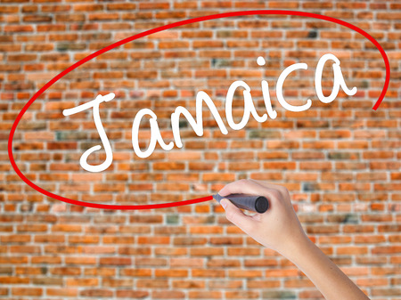 Woman Hand Writing Jamaica  with black marker on visual screen. Isolated on bricks. Business concept. Stock Photo Stock Photo