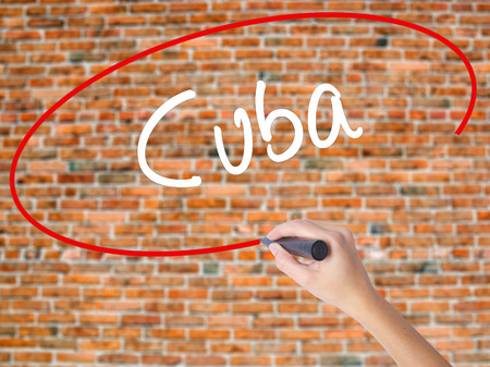 Woman Hand Writing Cuba with black marker on visual screen. Isolated on bricks. Business concept. Stock Photo