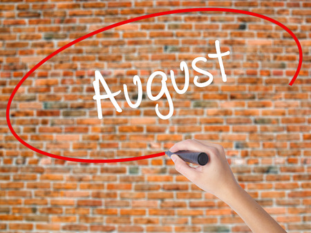 Woman Hand Writing August  with black marker on visual screen. Isolated on bricks. Business concept. Stock Photo Stock Photo