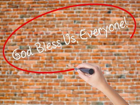 Woman Hand Writing God Bless Us, Everyone! with black marker on visual screen. Isolated on bricks. Business concept. Stock Photo