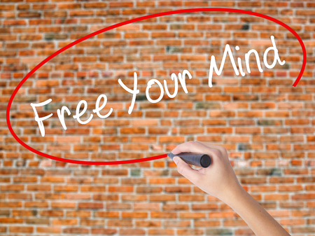 position d amour: Woman Hand Writing Free Your Mind with black marker on visual screen. Isolated on bricks. Business technology, internet concept. Stock Image Banque d'images
