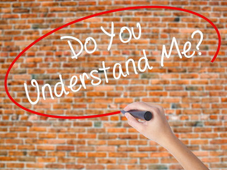 Woman Hand Writing Do You Understand Me? with black marker on visual screen. Isolated on bricks. Business concept. Stock Photo