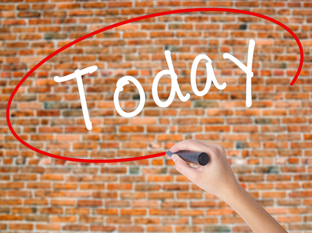Woman Hand Writing Today with black marker on visual screen. Isolated on bricks. Business concept. Stock Photo