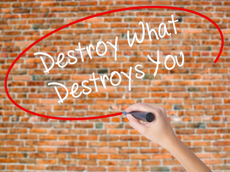 Woman Hand Writing Destroy What Destroys You with black marker on visual screen. Isolated on bricks. Business concept. Stock Photo