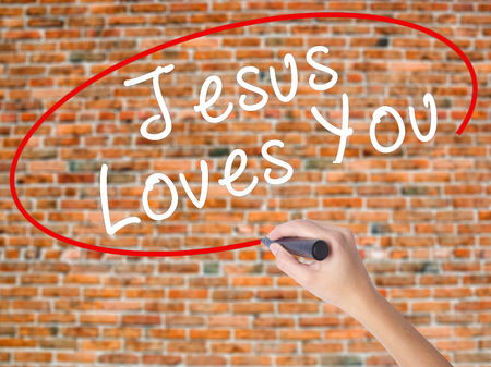 testament schreiben: Woman Hand Writing Jesus Loves You with black marker on visual screen. Isolated on bricks. Religion, technology, internet concept. Stock Image Lizenzfreie Bilder