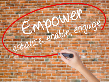 Woman Hand Writing Empower enhance, enable, engage with black marker on visual screen. Isolated on bricks. Business concept. Stock Photo