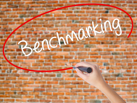 Woman Hand Writing Benchmarking  with black marker on visual screen. Isolated on bricks. Business concept. Stock Photo