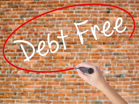 Woman Hand Writing Debt Free with black marker on visual screen. Isolated on bricks. Business concept. Stock Photo Stock Photo