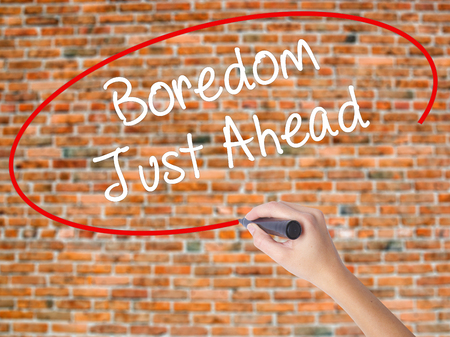 Woman Hand Writing Boredom Just Ahead with black marker on visual screen. Isolated on bricks. Business concept. Stock Photo Stock Photo