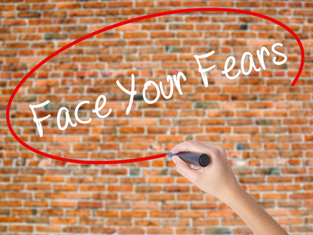 advise: Woman Hand Writing Face Your Fears with black marker on visual screen. Isolated on bricks. Business concept. Stock Photo Stock Photo