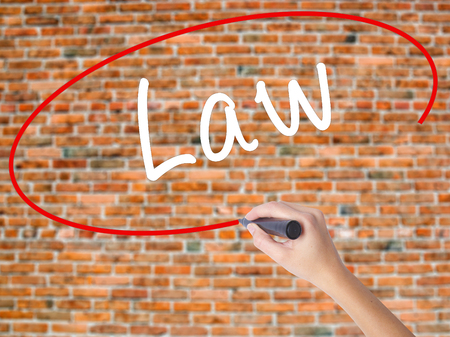 Woman Hand Writing Law with black marker on visual screen. Isolated on bricks. Business concept. Stock Photo Stock Photo