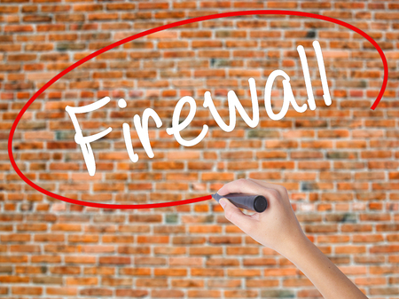 Woman Hand Writing Firewall  with black marker on visual screen. Isolated on bricks. Business concept. Stock Photo