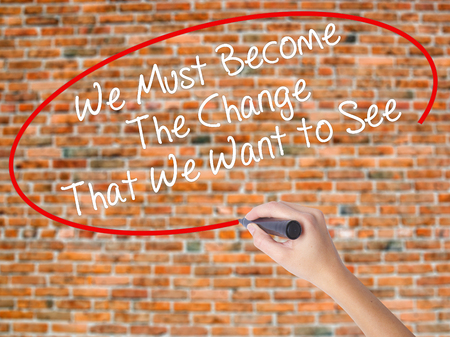 Woman Hand Writing We Must Become The Change That We Want to See with black marker on visual screen. Isolated on bricks. Business concept. Stock Photo