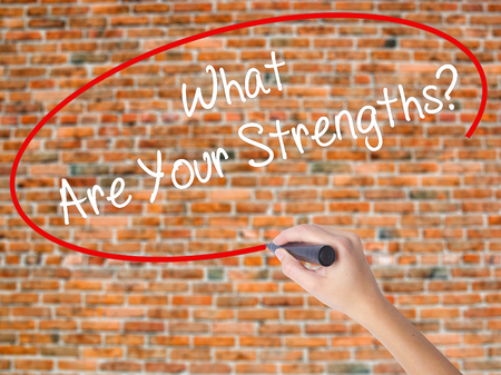 Woman Hand Writing What Are Your Strengths? with black marker on visual screen. Isolated on bricks. Business concept. Stock Photo