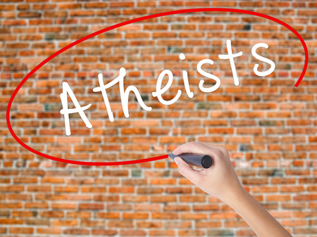 Woman Hand Writing Atheists with black marker on visual screen. Isolated on bricks. Business concept. Stock Photo