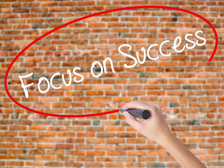 Woman Hand Writing Focus on Success with black marker on visual screen. Isolated on bricks. Business concept. Stock Photo Stock Photo