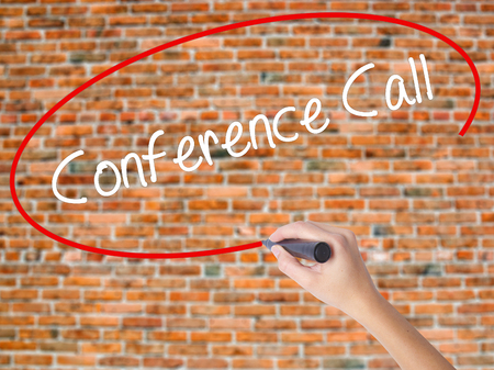 Woman Hand Writing Conference Call with black marker on visual screen. Isolated on bricks. Business, technology, internet concept. Stock  Photo