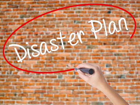 Woman Hand Writing Disaster Plan with black marker on visual screen. Isolated on bricks. Business concept. Stock Photo