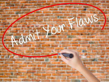 Woman Hand Writing Admit Your Flaws with black marker on visual screen. Isolated on bricks. Business concept. Stock Photo Stock Photo