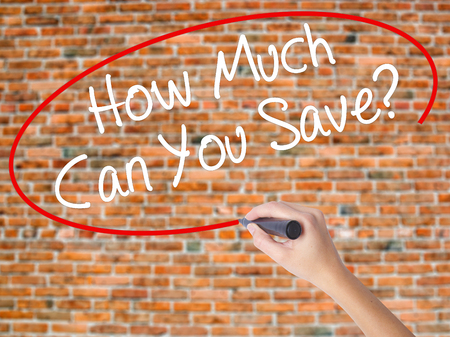 budgetary: Woman Hand Writing How Much Can You Save? with black marker on visual screen. Isolated on bricks. Business concept. Stock Photo