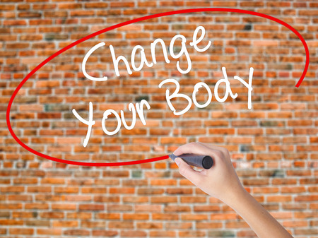 muscle gain: Woman Hand Writing Change Your Body with black marker on visual screen. Isolated on bricks. Business concept. Stock Photo